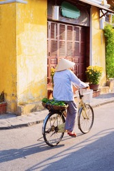 Cityscape with senior woman riding bicycle on street in Old city of Hoi An in Southasia in Vietnam. Elderly lady in Vietnamese hat on bike in Hoian.