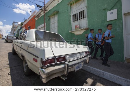 CIUDAD BOLIVAR, VENEZUELA, APRIL 9: Old wreck car parked in the old colonial city of Ciudad Bolivar with kids walking back from the school dressed in their blue uniform. Venezuela. April 9, 2015.