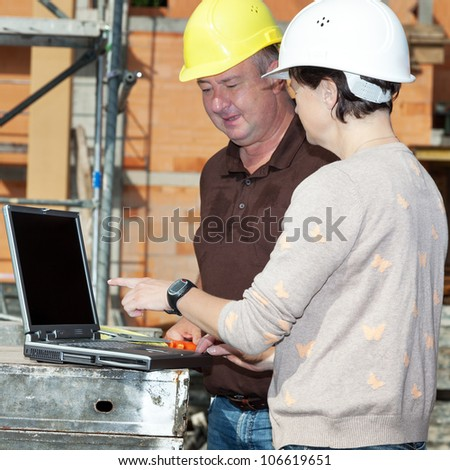 Civil engineer and construction worker looking at the laptop