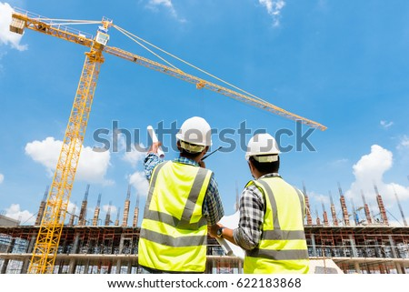 Civil engineer checking work with walkie-talkie for control and management in the construction site or building site of highrise building #622183868