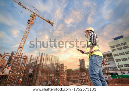 Civil engineer or architect with hardhat on construction site checking schedule on tablet computer.Foreman worker with tablet computer wear construction uniform with structure site work background ストックフォト ©