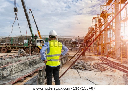 Civil Engineer supervised the construction of a tower crane and pile of concrete on construction sites in operation.