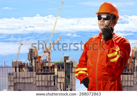 Civil engineer use radio communication control working at high building construction site