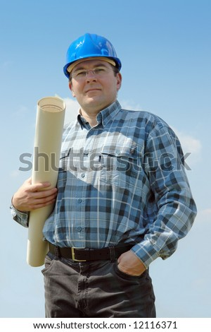 Civil engineer wearing blue helmet posing with roll of building plan over blue sky
