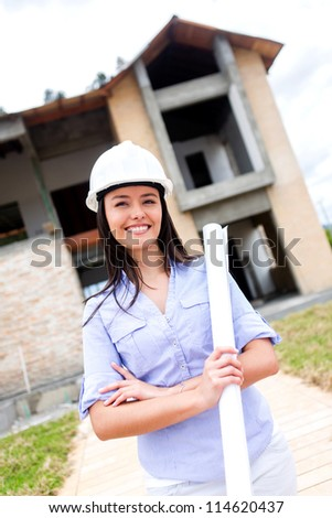 Civil engineer with blueprints at a construction site