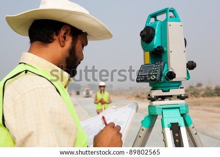 civil engineer working at a construction site, surveyor doing the survey at construction site