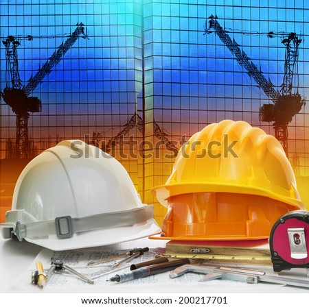 civil engineer working table with safety helmet and writing instrument against beautiful dusky sky and crane construction site