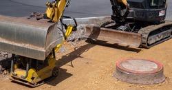 Civil engineering excavator on a sidewalk construction site