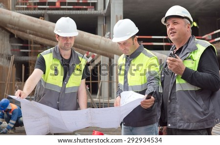 Civil engineers and senior foreman at construction site are inspecting ongoing construction works according to design drawings.