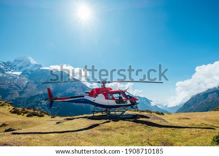 Civil helicopter landed in high altitude Himalayas mountains. Thamserku 6608m mountain on the background. Namche Bazaar, Nepal. Safety air transportation and travel insurance concept image.