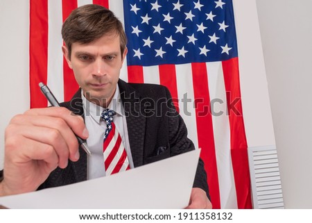 Civil servant next to USA flag. He fills out some documents. Civil servant at work. Work in public service. Bureaucracy in USA. Concept - filling out reports for the American government.