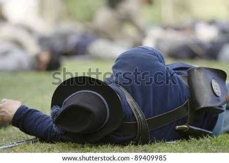 Civil War reenactor plays dead as a Union Army casualty on the field of battle.