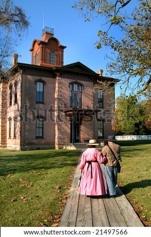 Civil War Weekend at Historic Washington Park in Old Washington, Arkansas.  War era couple stroll toward old federal courthouse.