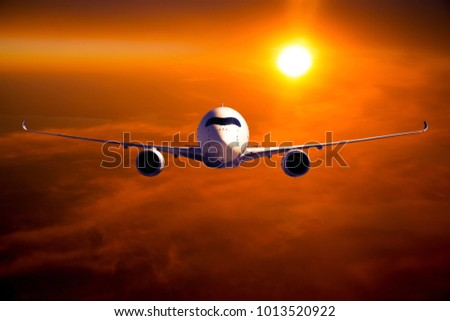 Civil wide body plane in flight. Aircraft flying on a high altitude above the clouds during flaming sunset. Airplane front view.