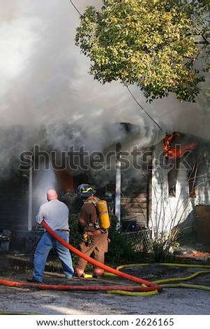 Civilian volunteer assisting fireman in putting out house fire