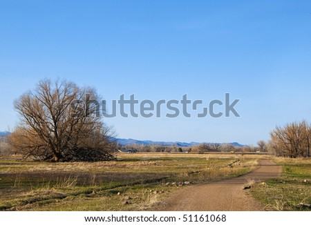 Civilization encroaches on a rural area with juxtaposed views of a quiet path and a distant crossing freeway. - stock photo