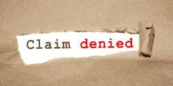 Claim Denied. phrase text under torn paper. Insurance and Warranty concept.