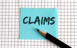 CLAIMS , the phrase is written on colored stickers, on a notepad background. Business