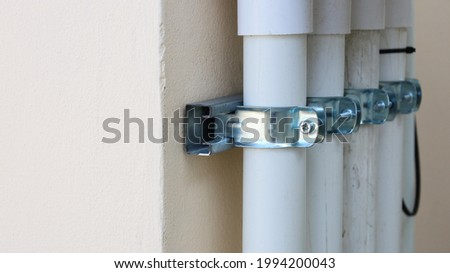 Clamp the conduits on the wall. Installation of IMC plastic conduit on the wall for electrical work that meets safety standards with copy space. Selective focus Stock photo ©