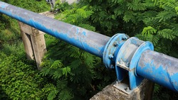 Clamps and nuts to hold old pipes on posts. A blue main water supply pipe with clamps and bolts connecting pipes on a concrete column base across the water canal with green plants. Selective focus