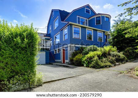 Clapboard siding house in blue color with red trim and stone wall trim