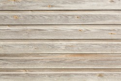 Clapboard, wood siding, timber cladding on an old building exterior, UK. Faded, weathered oak