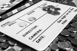 Clapperboard with coins above and on it creating a relation between filmmaking and business [Black and White version]