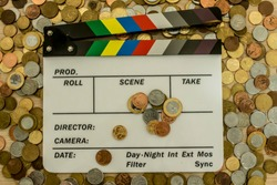 Clapperboard with many coins surrounding, above and on top of it