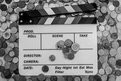 Clapperboard with many coins surrounding, above and on top of it [Black and White version]