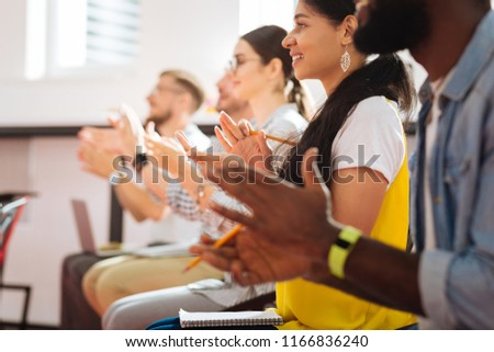 Clapping. Cheerful excited students applauding and looking at their teacher after passing their final exam