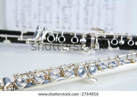 Clarinet and Silver flute with sheet music background - stock photo