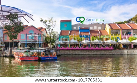 CLARKE QUAY, SINGAPORE - AUGUST 17, 2009:  Leisure boats moored in the Singapore River alongside the colorful buildings of Clarke Quay.