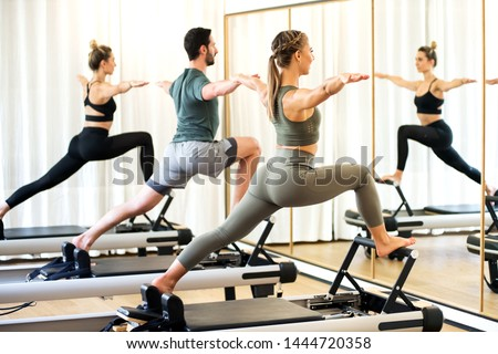 Class in a gym doing pilates standing lunges on reformer beds to stretch and tone the muscles reflected in a wall mirror Stockfoto ©