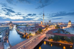 Classic aerial view of Berlin skyline with famous TV tower and Spree river in beautiful post sunset twilight during blue hour at dusk with dramatic clouds in summer, central Berlin Mitte, Germany