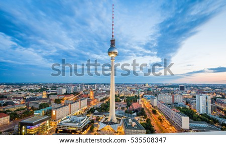 Classic aerial wide-angle view of Berlin skyline with famous TV tower at Alexanderplatz and dramatic cloudscape in beautiful twilight during blue hour at dusk in summer, central Berlin Mitte, Germany