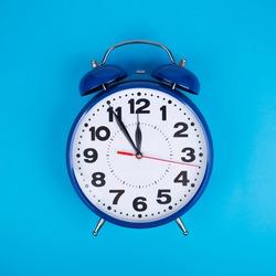 Classic alarm clock on light blue background