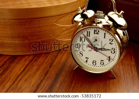 Classic alarm clock shot on wood table with wooden basket and box, space for copy
