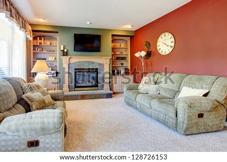 Classic American cozy living room interior with fireplace and red wall.