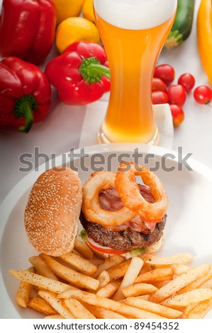 classic american hamburger sandwich with onion rings and french fries,glass of  beer and fresh vegetables on background