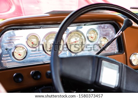 classic antique car black steering wheel and brown Dashboard close up, simple old style cars interior, Speed Counter, tachometer and other Counters