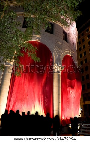 Classic architecture with flowing red curtains.  The silhouettes of the crowd are seen all around.