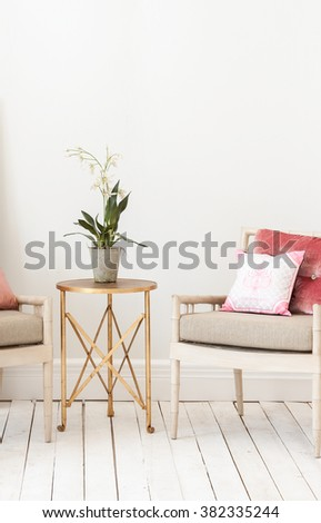 classic armchair  pillow and gold coffee table vase of flower with wooden floor behind white wall interior style