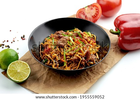 Classic Asian street food - udon wok noodles with pork, vegetables in sweet and sour sauce, served in a black plate. white background Zdjęcia stock ©