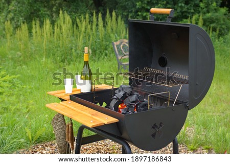 Classic Barrel Grill Appliance On The Backyard Lawn. Outdoor BBQ Grill Appliance. Barbeque Charcoal Barrel Flaming Hot Grill Ready For Cooking Cookout Food On Backyard Lawn. Garden Party Concept.