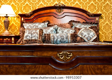 Classic bedroom detail with luxurious bed and stylish vintage decorated wall