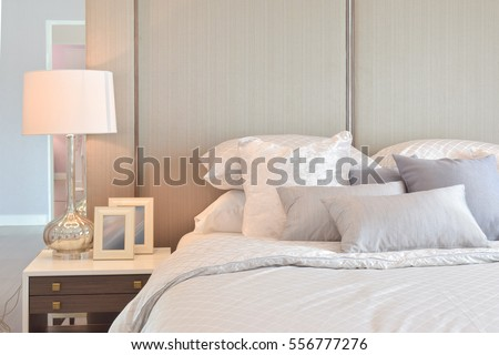 Classic bedroom interior with pillows and reading lamp on bedside table #556777276