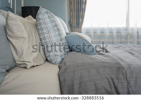 classic bedroom style with row of pillows on bed #328883516