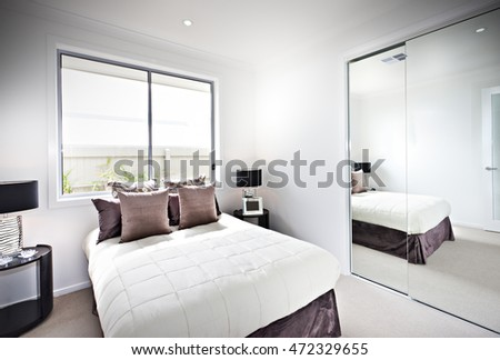 Classic bedroom with windows and lamps beside a mirror, the sunlight gave the lights to the room through the glass panel #472329655