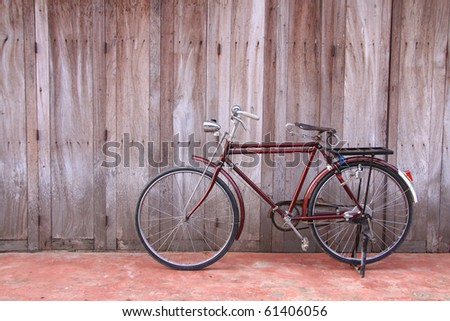 Classic bicycle parked against wooden wall