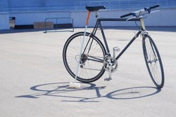 classic bike big with a stick for polo stands near a bicycle on the asphalt theme of polo and other games and sports